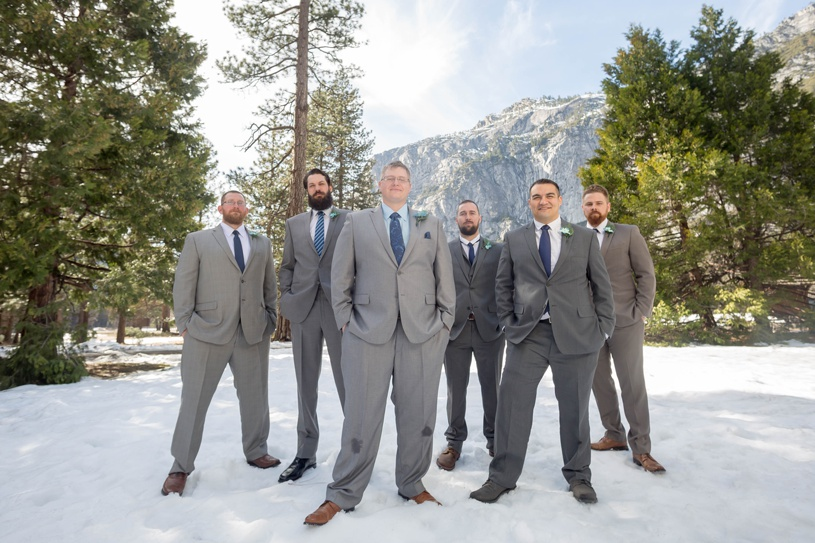 groomsmen in snow during winter at yosemite valley chapel by matthew leland photography
