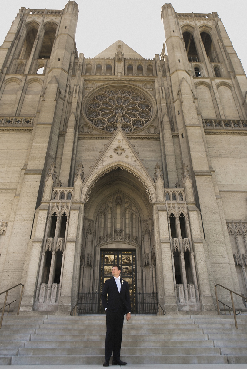 Groom standing in front of a San Francisco cathedral for his Dogpatch winery wedding by Matthew Leland Photography
